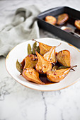 Baked pears with bay leaves on a plate and in a baking dish