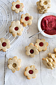 Flower-shaped Linzer Plätzchen (nutty shortcrust jam sandwich biscuits with holes on top) with raspberry jam