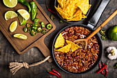 Chili con carne in frying pan on dark wooden background
