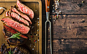Sliced grilled marbled meat steak Filet Mignon, seasonings, fork, wooden cutting board