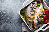 Baked fish dorado with green asparagus and tomatoes in white ceramic baking pan on gray rustic concrete background