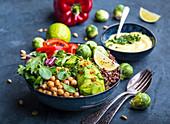 Buddha Bowl mit Kichererbsen, Avocado, Quinoa, Spinat, Rosenkohl und Paprika