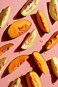 Various melon slices on a pink background