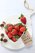 Fresh strawberries in a heart bowl with a message, on a white board