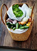 A basket bag with lettuce, vegetables, lemons, milk, cream and oatmeal