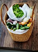 Basttasche mit Kopfsalat, Gemüse, Zitronen, Milch, Sahne und Haferflocken