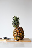 Pineapple on a cutting board with a knife