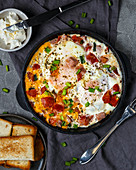 Roasted eggs with ham, tomatoes and green onions