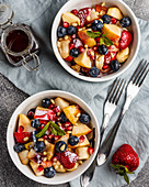 Fruit salad with apples, bananas, strawberries, blueberries, pomegranate seeds, pine nuts, yogurt and honey