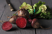 Red sugar beetroots on stem with green leaves