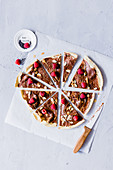 Chocolate pizza with raspberries and almond flakes