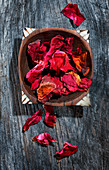Red rose petals in a wooden bowl