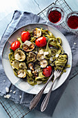 Green tagliatelle with grilled zucchini, cocktail tomatoes and parmesan on a blue wooden background