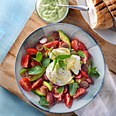 Avocado and tomato salad with grapes, mozzarella, mint and mint yoghurt dressing