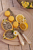 Lemon macarons, yellow dragon fruit and halved lemons on a plate