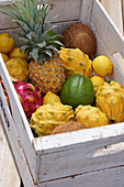 Various exotic fruits in a white wooden box