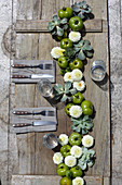 Garland of white pom pom dahlias, green tomatoes and houseleeks on rustic table
