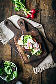 Crostino mit Mozzarella, Salat, Radieschen und Essblüte