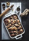From above tray with fresh homemade cinnamon buns and wooden rolling pin on white marble board