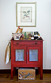 Bottles of olive oil, olives and kitchen utensils on red-painted cabinet