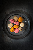 Various macarons on a grey plate