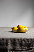 Appetizing lemons with shiny yellow peel in glass plate on grey linen tablecloth