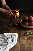 Tasty ripe peaches in plate and hands peeling peach