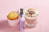 Hot chocolate and coconut drink with cinnamon, coconut milk and grated coconut, with biscuits