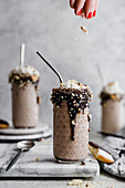 Black and white milkshake, a hand sprinkles a topping on a milkshake