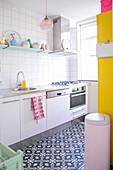 Weiße Küche mit schwarz-weißem Fliesenboden und knallbunten Farbakzenten