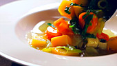 Serving vegetable soup on a plate