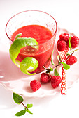 A red smoothie made from raspberries, papaya, grapefruit, maple syrup and cardamom