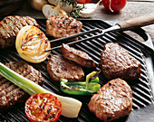 Various meats and vegetables on a grill
