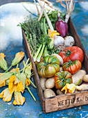 A crate of vegetables including tomatoes, potatoes and courgette flowers