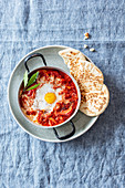 Shakshuka with smoked peppers, harissa and unleavened bread (Levant cuisine)