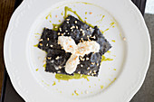 Ravioli with cuttlefish ink stuffed with croaker and broad beans on velvety chickpea