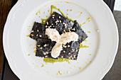 Tintenfischravioli gefüllt mit Umberfisch und dicken Bohnen