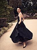 Dunkelhaarige Frau in schwarzem, schulterfreiem Abendkleid