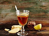 Canadian apple punch with whisky, cinnamon, lemon and biscuits on a wooden surface
