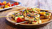 Grilled marinated halloumi wrapped in courgette on wooden sticks