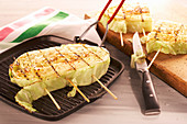 Sliced, grilled shite cabbage in a grill pan with a knife