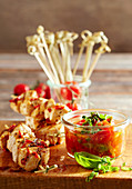 Grilled, marinated chicken skewers with cherry tomato sauce and basil