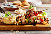 Grilled Arabic lamb skewers with a red lentil salad and white bread on a wooden board