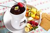 A mini chocolate fondue for dessert with fresh fruit and biscuits