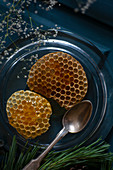 Honeycomb oozing honey on glass plate with silver spoon
