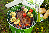 Rib-eye steak with tomatoes and rosemary potatoes on a barbecue