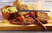 Grilled beef steaks with a vegetable salad and bread, cherry tomatoes, rosemary and a vintage copper pot