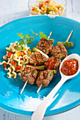 Grilled turkey skewers with a spoonful of tomato chutney and pasta salad