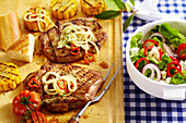 Grilled pork collar steaks in a beer marinade with grilled corn cobs and a colourful salad