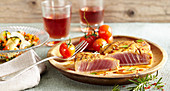 Grilled tuna steak with cherry tomatoes and courgette salad on a wooden plate
